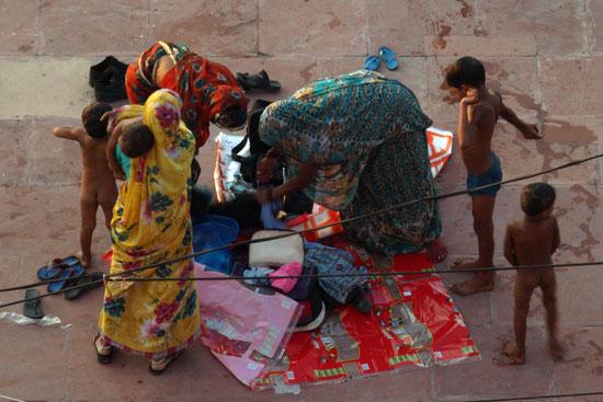 Madres despiertan a sus hijos y los bañan en el Ganges al amanecer en Haridwar. Allí en la calle han pasado la noche./ C.E.L.