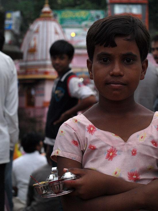 Una niña pinta tikas a la gente que acude a la puja por una rupia. Haridwar./ C.E.L.