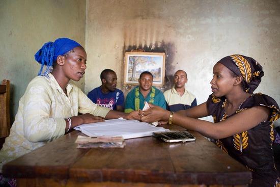 Dos mujeres tanzanas gestionan, en el año 2010, parte de los fondos con los que participan en un sistema empresarial cooperativo ante la mirada de tres hombres. /Foto: J. Marcos
