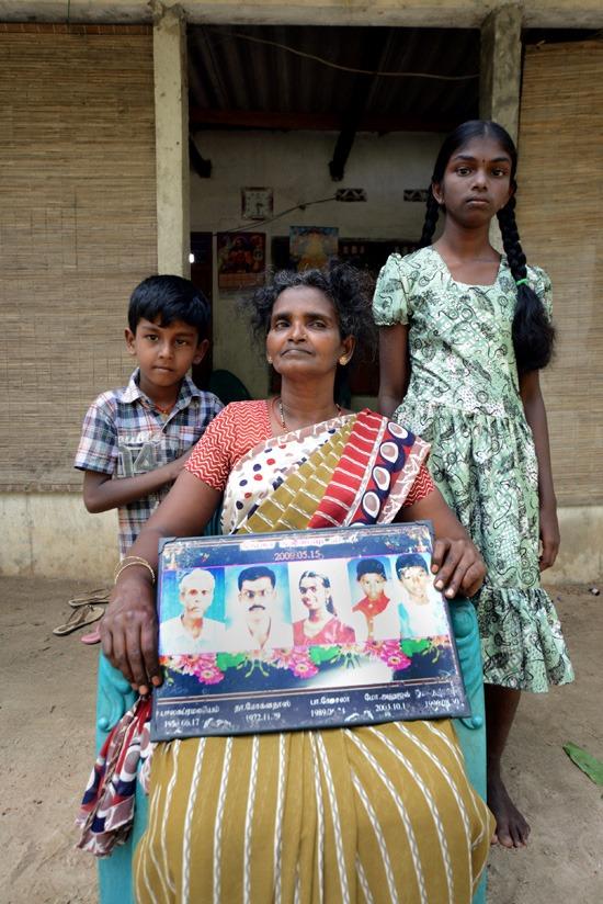 Balasubramaniam se niega a llevar el 'bindi' y, por eso, rara vez sale de casa. Posa allí con sus los dos nietos que sobrevivieron al bombardeo en el que perdió a los miembros de su familia que aparecen en el marco que sujeta.- Zigor Aldama