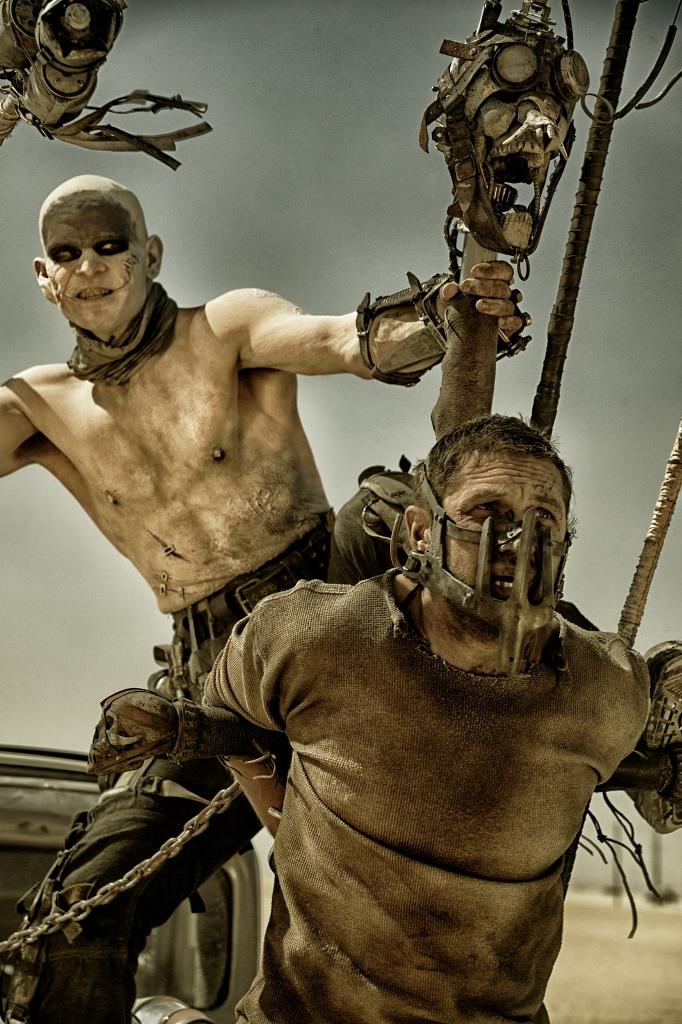Furiosa huye y Max queda enganchado a un coche con una máscara de hierro que le hace vulnerable