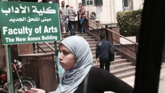 Una mujer camina frente a la Facultad de Arte