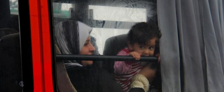 Una madre y su hija esperan en el autobús a la entrada del campo de registro de Rözske, en Hungría./B.L.