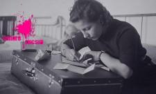 Sangre Fucsia Mujer escribiendo una carta en cima de su maleta