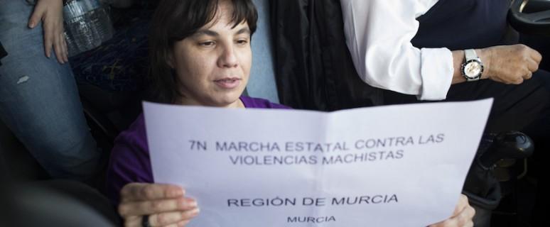 Una de las integrantes del Fórum de Política Feminista de la Región de Murcia coloca el cartel identificativo del autobús ©Salvador Fenoll/OM Colectivo