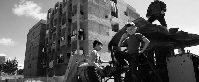 Niños sirios jugando entre maquinaria abandonada a las afueras de Sidon. Líbano.