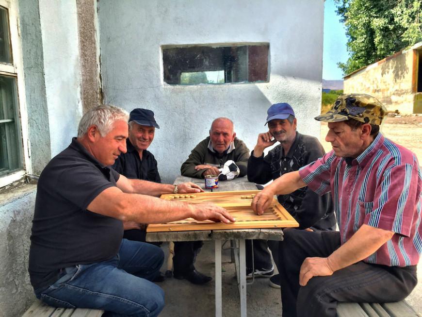 Garik (izq.) juega al nardi con otros hombres. El de la derecha, Samvel, ya no recuerda en cuántos secuestros ha participado./ V.M.