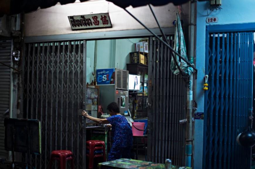 Una mujer entra en su casa del distrito de Samphanthawong donde una televisión emite una telenovela/ Foto: Walter Astrada