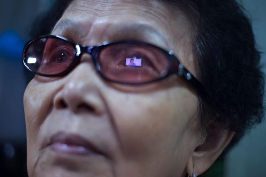 Una pantalla de televisión es reflejada en las gafas de una mujer que mira una telenovela en el interior de su casa en el barrio de Chinatown de Bangkok / Foto: Walter Astrada