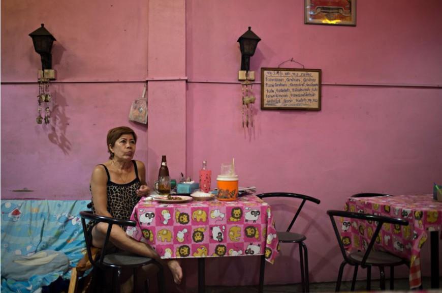 Una mujer mira una telenovela mientras cena en el interior de un restaurante en el distrito de Samphanthawong de Bangkok / Foto: Walter Astrada