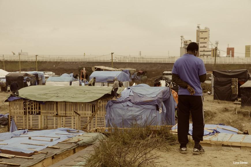 Un refugiado busca cobertura de móvil en una parte alta del campamento. Al fondo una valla separa el campamento de la carretera que lleva al puerto. / Foto: Luna Gámez