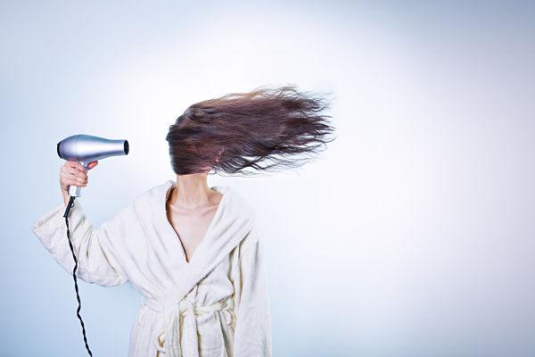 Una persona se seca el cabello largo con un secador y el cabello le cubre todo el rostro