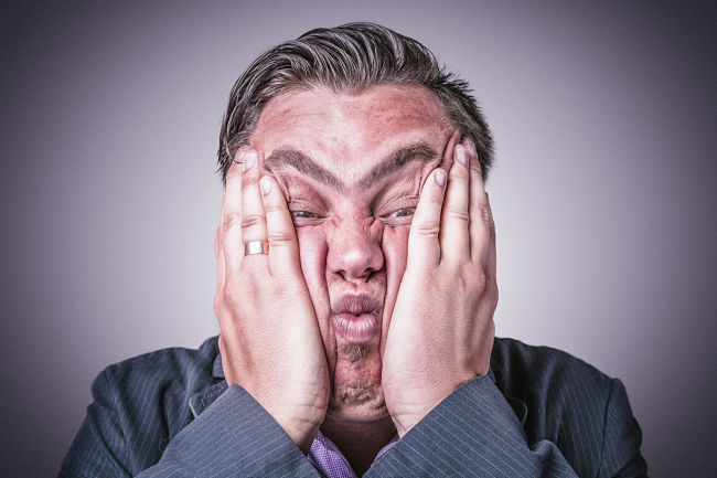 Un hombre hace muecas presionando sus mejillas con sus manos