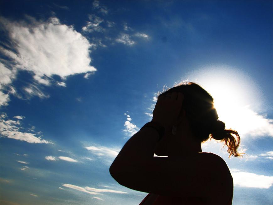 Mujer a contraluz mirando al cielo