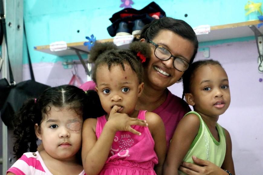 Rosana Nascimento, psicóloga y coordinadora de la Casa de Apoyo a la Infancia, posa con algunas de las niñas haitianas que pasan el día en esta guardería./ Foto: Luna Gámez.