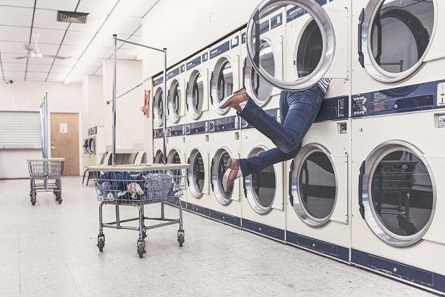 Una mujer se introduce dentro de una de las lavadoras de la lavandería