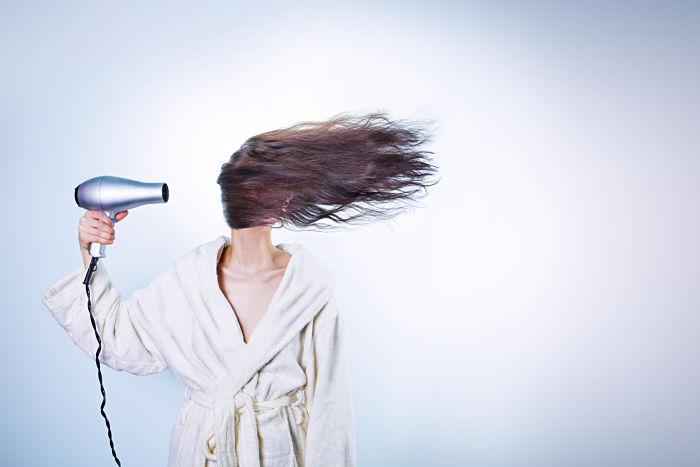 Una mujer se seca el pelo con secador de tal potencia que el pelo le cubre todo el rostro
