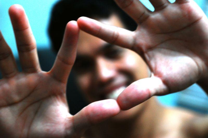 Un chico hace la forma del triángulo con las manos