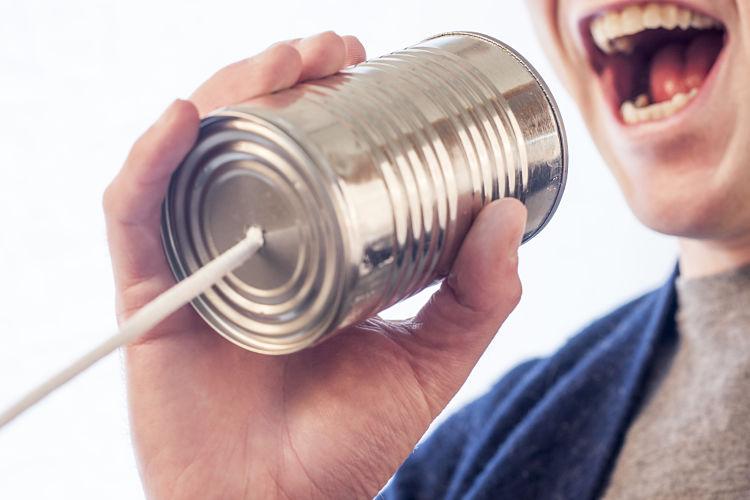 Una persona grita dentro de una lata que va conectada a una cuerda