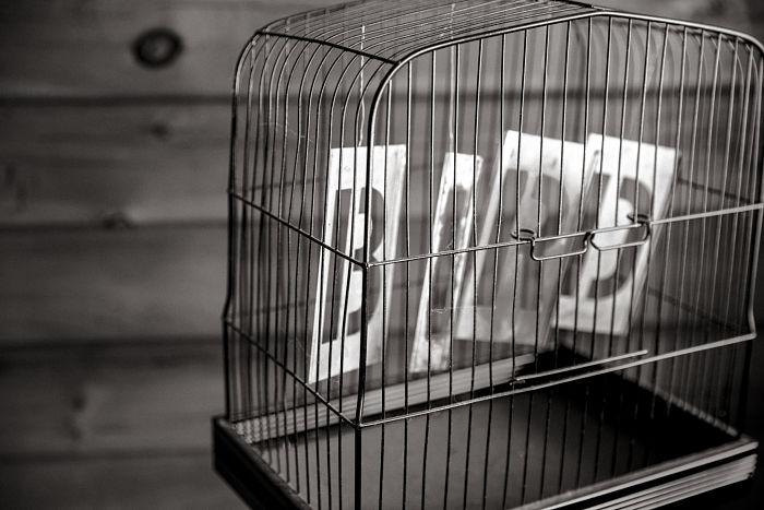 """Fotografía en blanco y negro de una jaula de pájaro que contiene un cartel en el que pone """"pájaro"""" en inglés"""