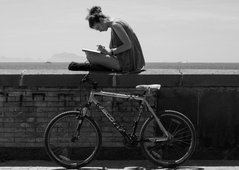 Una mujer escribe a mano en un cuaderno y debajo, apoyada en un muro, hay una bicicleta