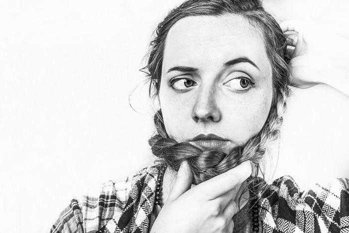 Una mujer cruza sus trenzas en la barbilla a modo de barba y tiene un aire pensativo