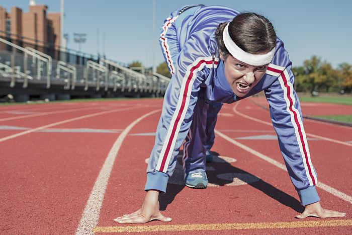 Una mujer se prepara para comenzar una carrera en la línea de salida y su expresión es de lucha