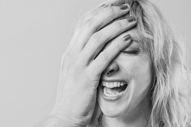 Una mujer se tapa el rostro con una mano mientras ríe