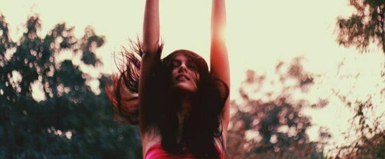 Una mujer extiende los brazos hacia el cielo en estado de clímax