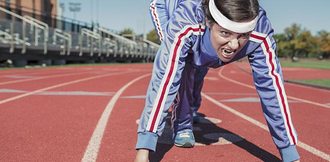 Una mujer se prepara para comenzar una carrera en la pista de atletismo con mirada agresiva