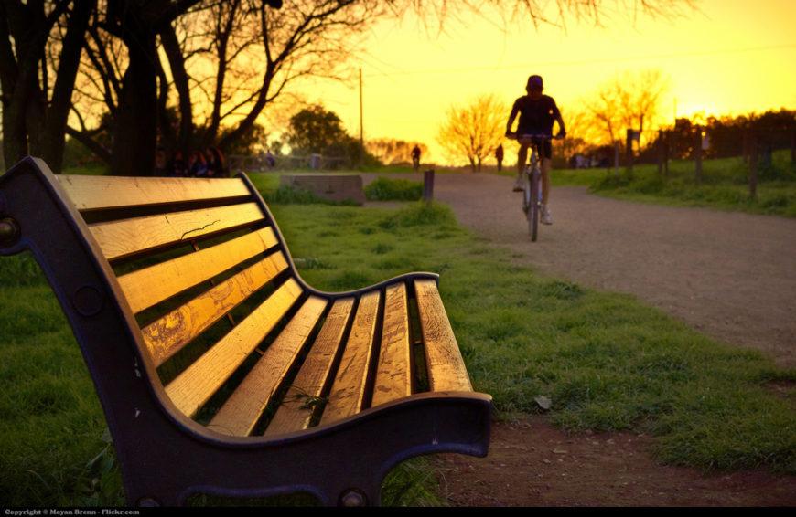 Imagen de un banco y un ciclista que avanza durante la puesta de sol