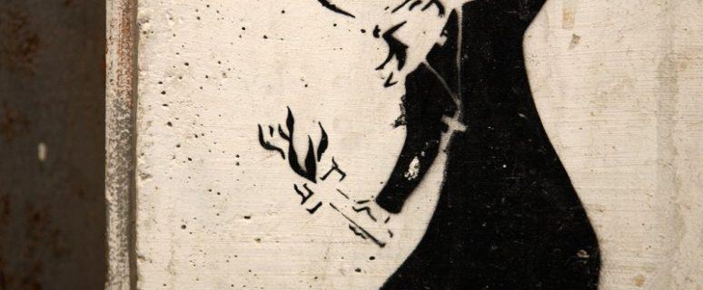 Grafitti de un obispo lanzando una cruz que arde en llamas