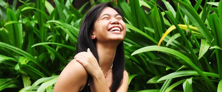 Una mujer sonríe y se abraza en un espacio natural