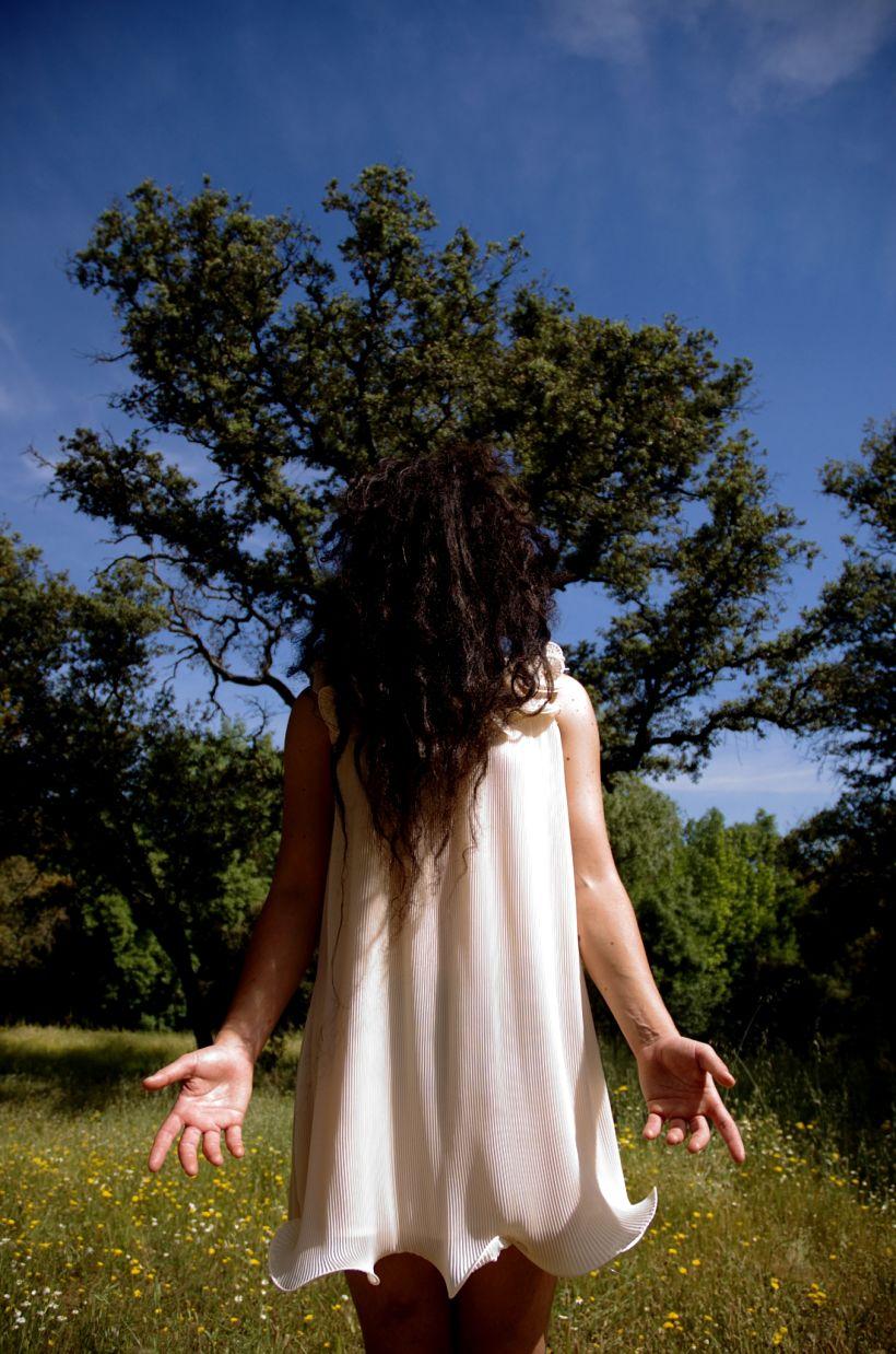 Un cuerpo posa frontalmente con un vestido en forma de campana y se cubre el rostro con toda su melena oscura