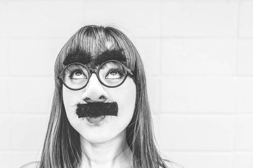 Una mujer lleva postizos de bigote y gafas con cejas