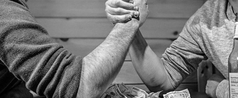 Dos hombres echan un pulso sobre una mesa cubierta de billetes