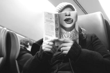 Alguien lee en el tren y se oculta el rostro con la portada de un libro en el que aparece una vampira lamiéndose los labios