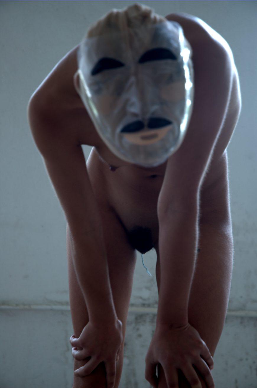 Un cuerpo menstruante desnudo cubre su rostro con una máscara