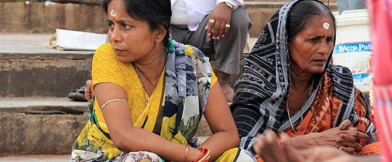 Dos mujeres hindús aparecen de fondo y en primer plano aparece la mano de alguien que pide limosna
