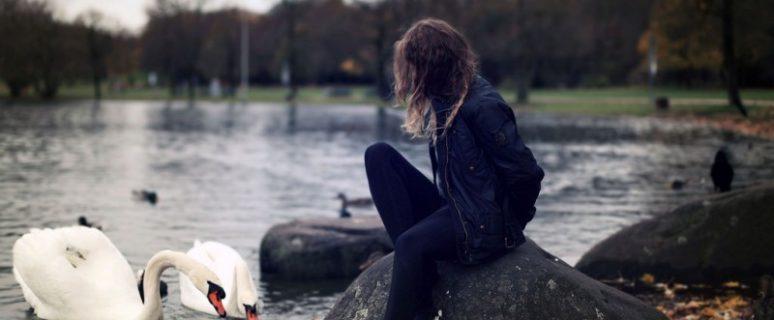 Una mujer agacha la cabeza en un lago, acompañada de dos cisnes