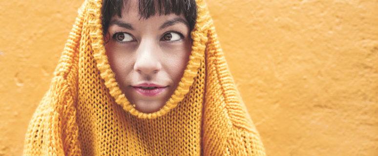 Una mujer cubre su cuerpo hasta la cabeza con un jersei, asomando solo el rostro