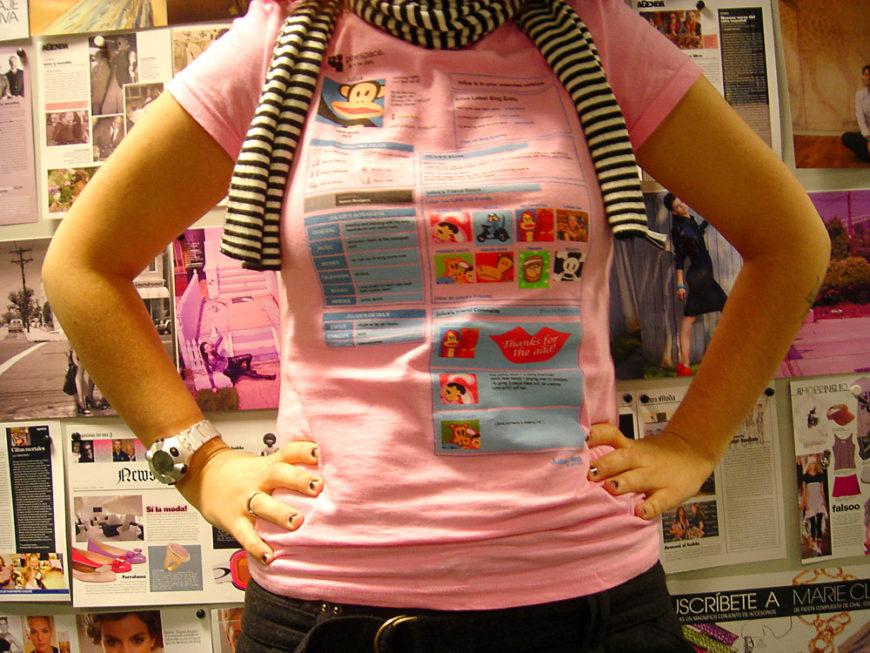 Una mujer aparece con los brazos en jarra y viste una camiseta rosa y una bufanda amarilla a rallas negras