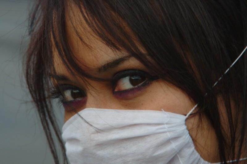 El rostro de una mujer que mira fijamente a cámara y que lleva la boca y la nariz cubiertas con una máscara sanitaria