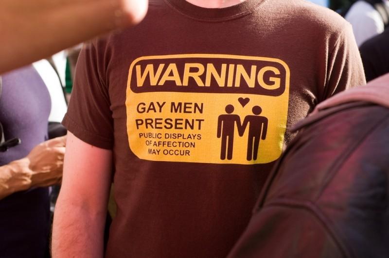 En la camiseta de un hombre se lee el mensaje: atención, gays presentes, muestras de afecto en público pueden ocurrir