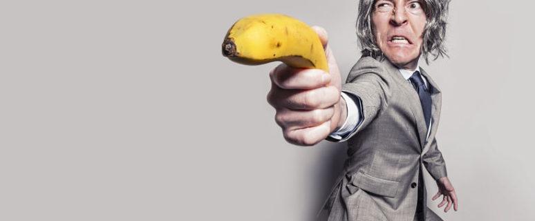 Un hombre vestido en traje apunta al objetivo con un plátano