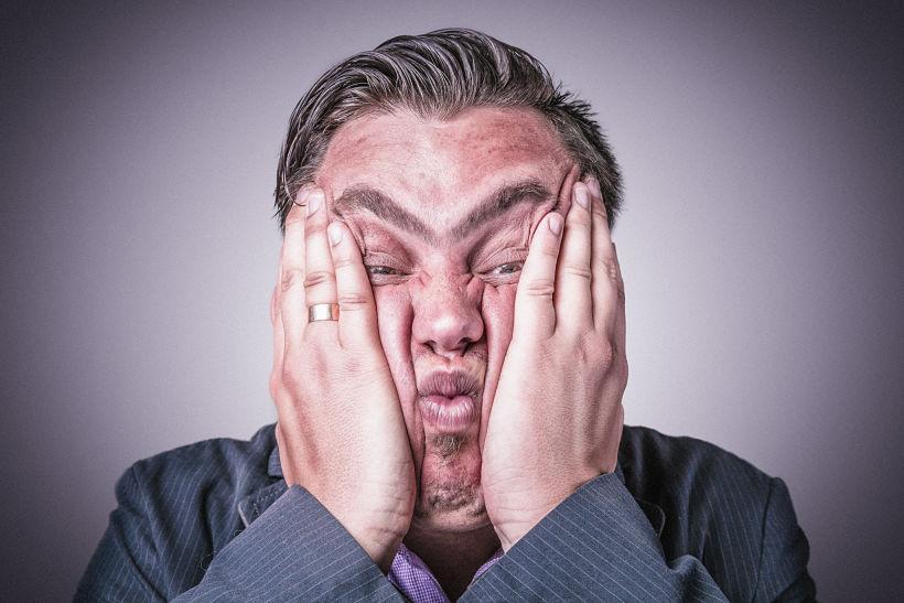Un hombre hace pucheros y se oculta el rostro con las manos
