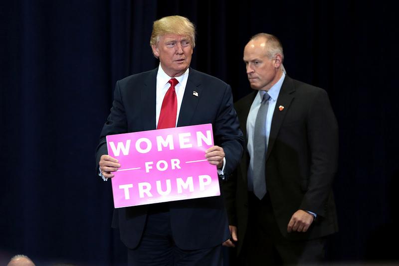 """Donald Trump sostiene un cartel rosa que reza """"Mujeres por Trump"""""""