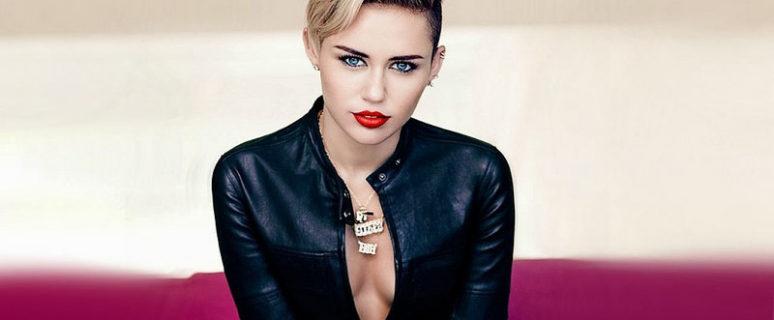 Miley Cyrus aparece sentada con una chaqueta de cuero negra y sobre fondo lila con una apariencia andrógina