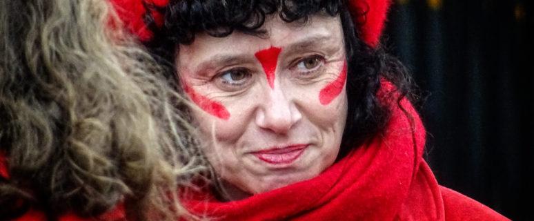 Rostro de una mujer de mediana edad vestida de rojo y con líneas rojas pintadas en la cara
