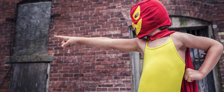 Unx niñx con disfrazadx de superhéroe señala a alguien